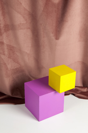 Two bright yellow and pink cubes in balance one on the other in front of an old pink velvet curtain. Minimum still life color photography? Stock Photo