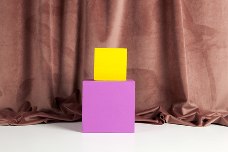 Two bright yellow and pink cubes placed one on the other in front of an old pink velvet curtain. Minimum and geometric still life color photography