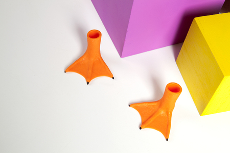 2 orange plastic duck legs and coloured cubes yellow and pink. Minimal and geometric still life color photography Stock Photo