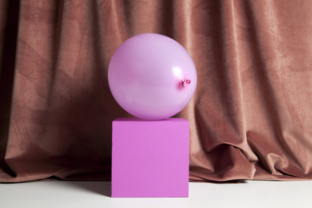 a pink inflatable balloon on a pink cube in front and under a pink velvet curtain. Color harmony. Minimal still life color photography