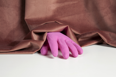 a pink inflated plastic household glove emerging from a pink velvet curtain. Color harmony. Minimal still life color photography Stock Photo
