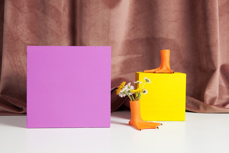 duck legs like vase with flowers inside and coloured cubes in front of a pink velvet curtain. Stockfoto