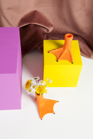 duck legs like vase with flowers inside and coloured cubes in front of a pink velvet curtain. Stok Fotoğraf