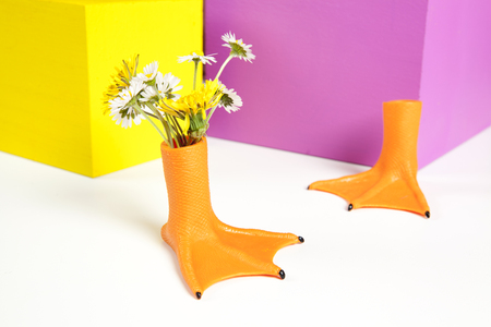 duck legs like vase with flowers inside and coloured cubes. Minimal still life color photography