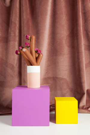 bicolor vase with sausages inside instead of flowers inside on colored cubes in equilibrium. Minimal still life color photography