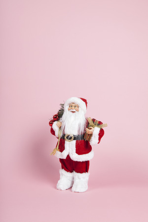 a santa claus figurine plush on a pink background. Color harmony. Minimal still life color photography Stock Photo