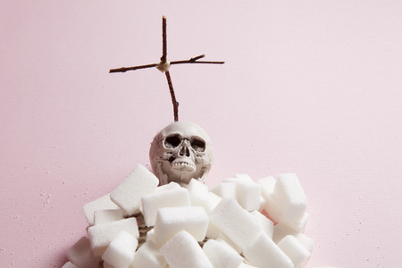 a skeleton covered with white sugar cubes like a tomb with a cross on a pink background and in front of a pink velvet curtain. Color harmony. Minimal still life color photography Stock Photo