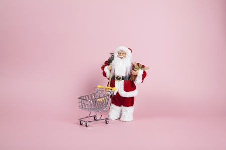 a santa claus figurine plush placed in front of a shopping trolleyon a pink background. Color harmony. Minimal still life color photography