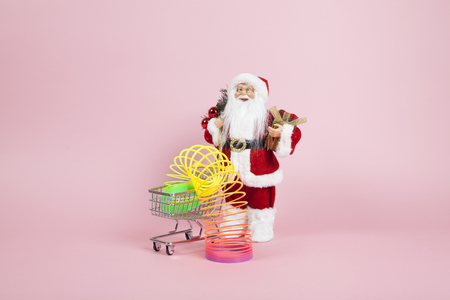 a santa claus figurine plush placed in front of a shopping trolley with rainbow spring inside on a pink background. Color harmony. Minimal still life color photography