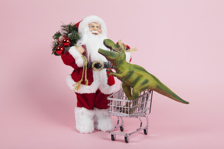 a santa claus figurine plush placed in front of a shopping trolley with tyrannosaurus plastic toy inside on a pink background. Color harmony. Minimal still life color photography