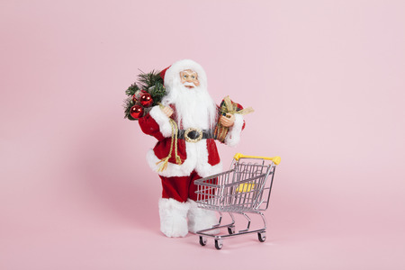 a santa claus figurine plush placed in front of a shopping trolley on a pink background. Color harmony. Minimal still life color photography