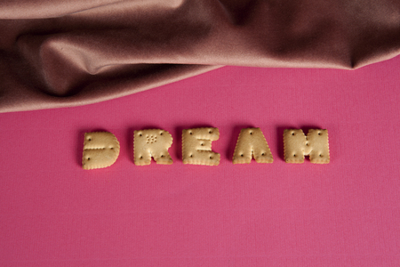 zoom of the word dream written in dry biscuit letters in front of a curtain of old pink velvet. Minimum color still life Stock Photo