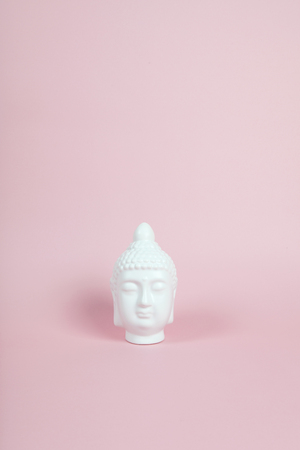 a white porcelain bouddha head on a pink and vibrant background. Minimum color still life