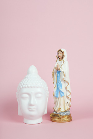 Icons of a white porcelain buddha head next to the Virgin Mary of Lourdes on a pink and vibrant background. Symbol of Living Together. Minimum color still life.