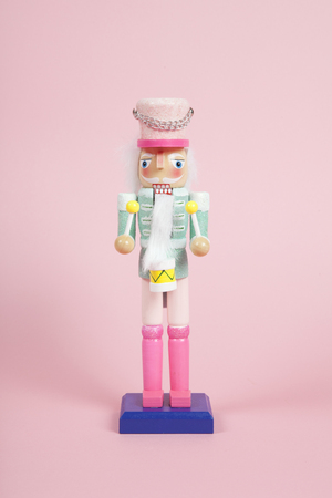 wood nutcracker figurine placed on a pink background. Color harmony. Minimal still life color photography