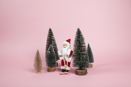 a Santa Claus figurine skiing among miniature firs on a pink background. Color harmony. Minimal still life color photography