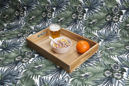 a quirky wooden tray serving a unhealthy breakfast on an exotic print of leaves background. Minimal still life color photography