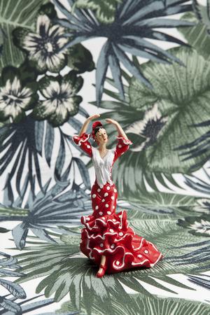 a flamenco dancer figurine on a tropical motif background. Minimal still life color photography