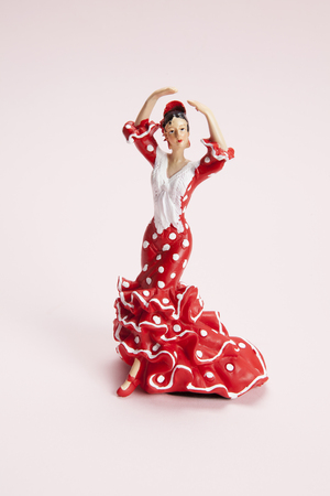 a flamenco dancer figurine on a pop pink background. Minimal still life color photography