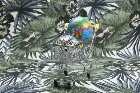 a disco ball and a planet earth in a supermarket shopping cart on a tropical motif background. Minimal still life color photography Stock Photo