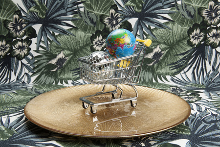 a disco ball and a planet earth in a supermarket shopping cart in a golden plate on a tropical motif background. Minimal still life color photography