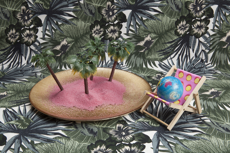 a golden plate with pink sand and mini plastic palm trees inside as well as a pink deckchair on a tropical printed background. Minimal still life color photography.pattern, leaves, palm, jungle,
