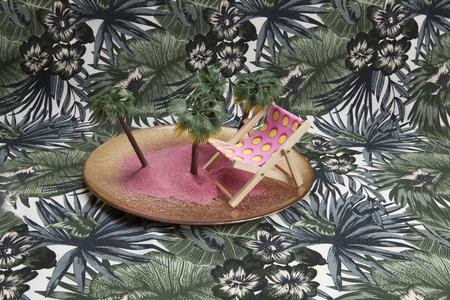 a golden plate with pink sand and mini plastic palm trees inside as well as a pink deckchair on a tropical printed background. Minimal still life color photography.pa Stock Photo