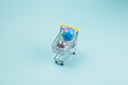 a disco ball and a planet earth in a supermarket shopping cart turquoiseon a turquoise background. Minimal still life color photography Standard-Bild