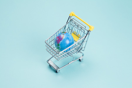 a planet earth in a supermarket shopping cart on a turquoise background. Minimal still life color photography Imagens