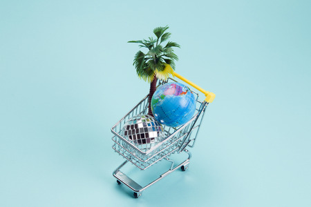 a disco ball, palm tree and a planet earth in a supermarket shopping cart turquoise on a turquoise background. Minimal still life color photography Stock Photo