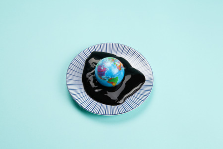 an antistress ball representing the planet earth drowned in an oil spill. Minimal still life color photography. Reklamní fotografie