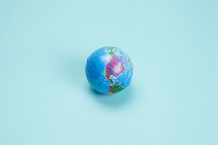 an antistress ball representing the planet earth, isolated on a plain turquoise background. Minimal still life color photography.