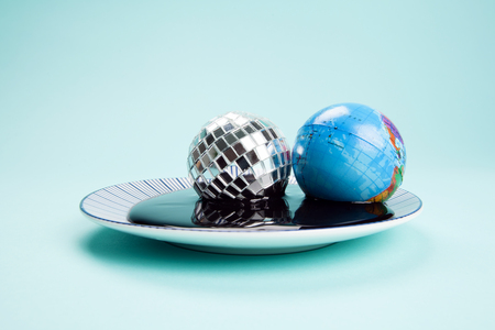 an antistress ball representing the planet earth near a disco ball drowned in an oil spill. Minimal still life color photography.