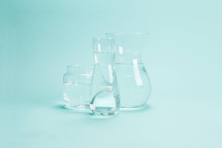 3 transparent glass vases filled with clear water on a turquoise background. Play of light and transparency. Minimal still life color photography