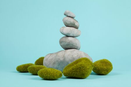 a pile of Zen stones in balance surrounded by moss rocks on a turquoise summer background. Minimal color still life photography. Stockfoto