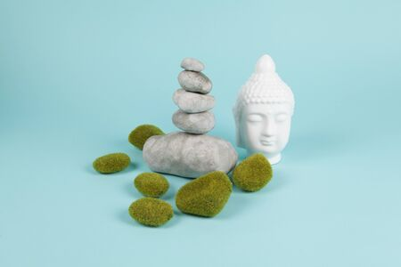 a pile of Zen stones in balance next to a Buddha's head surrounded by sparkling rocks on a turquoise summer background. Minimum color still life.