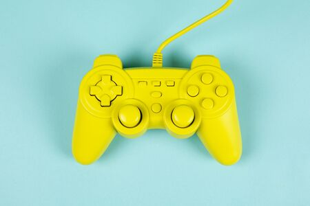 a yellow painted video game controller on a plain turquoise background. Minimal color still life photography Banque d'images