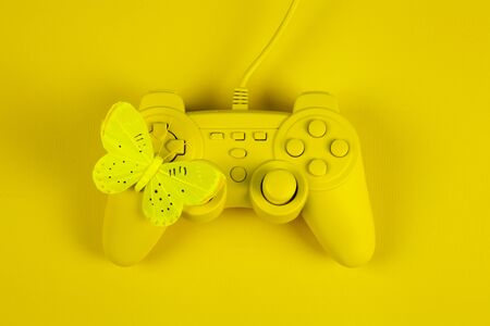 a yellow painted video game controller and a yellow butterfly on it on a plain yellow background. Minimal color still life photography Standard-Bild