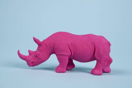 a pink fuschia rhinoceros, set on a blue background. Pop atmosphere. minimal color still life photography pop atmosphere. Minimal color still life photograph