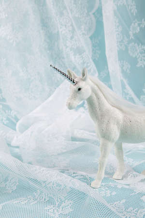 a white sequined unicorn on a lace curtain on a blue background. Minimal color still life photography