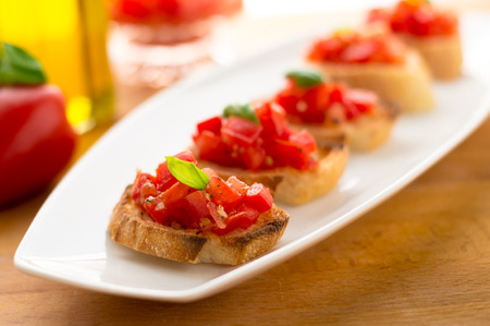 Plate of Bruschetta. Italian tomato bruschetta served as appetizer, made with fresh ingredients like tomatoes, garlic, basil, bread and olive oil.