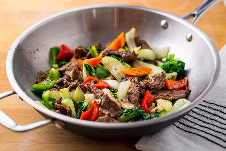 Flank steak beef, peppers, onions and bok choy stir fried in an asian wok. It's easy to eat healthy vegetables in a delicious stir fry! Stockfoto