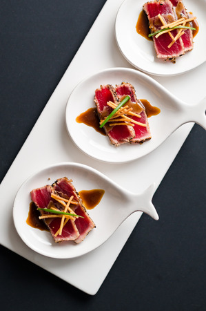 Tuna Tataki is a Japanese dish which consist of briefly seared tuna steak in thin slices. Served as appetizer with brandy sauce and garnish on a dark background.