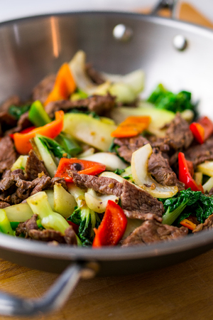 asian food: Healthy vegetable & beef stir-fry. Made with flank steak, peppers, onions and bok choy stir fried in an asian wok.