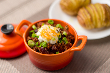 chili sauce: Fresh homemade bowl of chili con carne with beans, sour cream, grated cheddar cheese and green onions. Served with hasselback potatoes on the side. Stock Photo