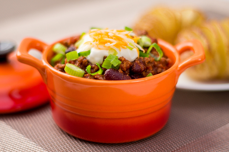 flatulence: Fresh homemade bowl of chili con carne with beans, sour cream, grated cheddar cheese and green onions. Served with hasselback potatoes on the side. Stock Photo