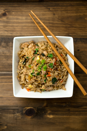 Basil chicken fried rice with chopsticks on a wooden background viewed from above. This thai inspired meal is perfect for a quick lunch or served as side dish.
