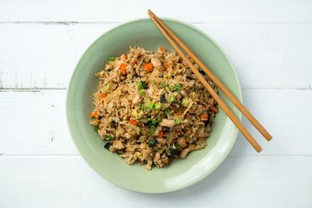 chinesisch essen: Basil Huhn gebratener Reis mit St�bchen auf einem wei�en h�lzernen Hintergrund von oben gesehen. Das Thai-inspirierte Mahlzeit ist ideal f�r ein schnelles Mittagessen oder als Beilage serviert. Lizenzfreie Bilder