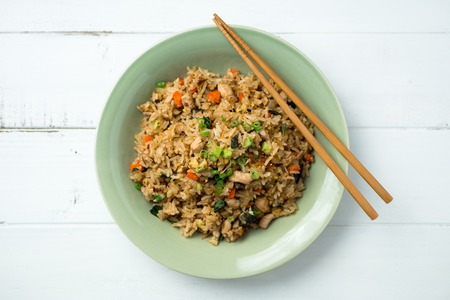 Basil chicken fried rice with chopsticks on a white wooden background viewed from above. This thai inspired meal is perfect for a quick lunch or served as side dish.