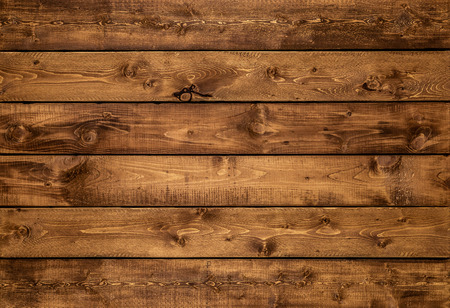 Medium brown wood texture background viewed from above. The wooden planks are stacked horizontally and have a worn look. This surface would be great as design element for a wall, floor, table etc…